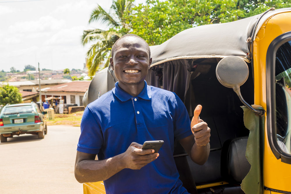cheerful african man standing next to his tuk tuk keke taxi smiling and using his smart phone giving a thumbs up